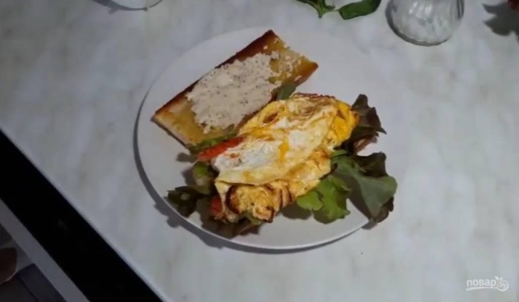 4. Далее подготовьте хлеб: смажьте его майонезом с горчицей, выложите на него листья салата. Затем аккуратно сверните омлет в рулет и выложите на листья салата.