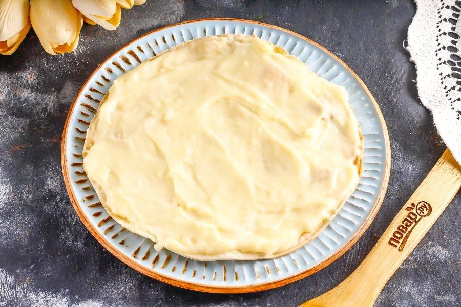 Выложите на тарелку первый корж и обильно смажьте его кремом. Сразу же отложите два коржа, они понадобятся для приготовления присыпки.