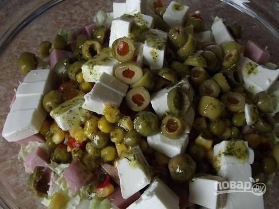 Оливки нарезаем шайбочками. У меня оливки, фаршированные перцем. Отправляем оливки в салатник и поливаем заправкой.