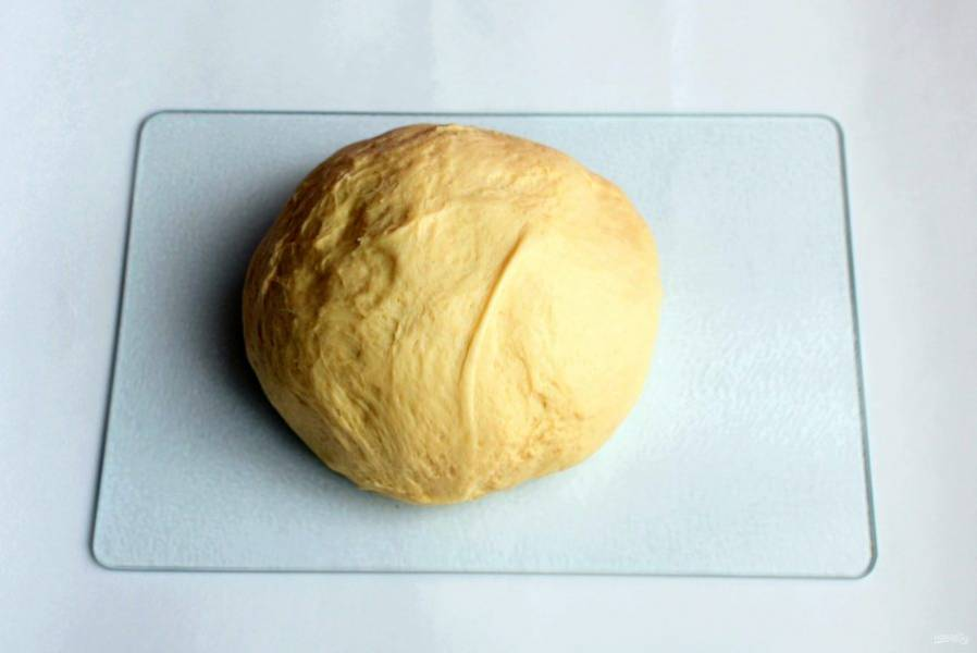 Просейте муку, добавьте дрожжи, соль и сахар. Влейте теплое молоко, добавьте масло и замесите густое тесто. Смажьте тесто маслом и уложите в миску под пленку. Дайте расстояться до увеличения объема в три раза.