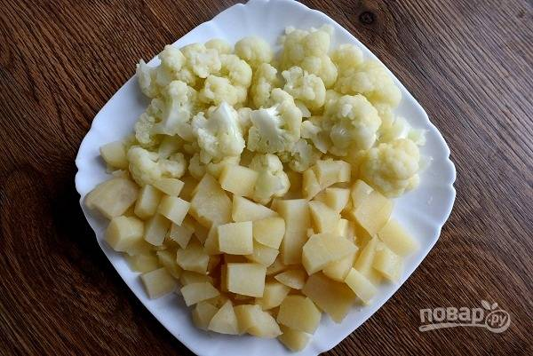Отварите картофель в мундире, остудите, очистите и нарежьте кубиками. Капусту бланшируйте в течение 2 минут, остудите и разберите на соцветия.