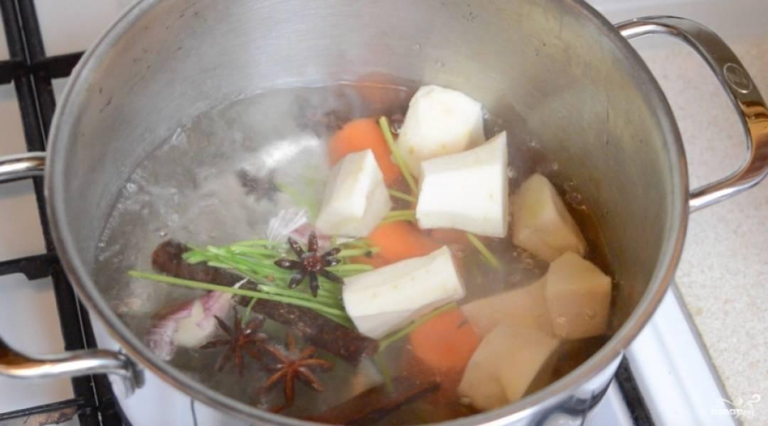 2. Тем временем доводим до кипения литр воды, а в нем - картофель, анис, перец, оставшийся чеснок и морковь. Когда закипит, убавим огонь и добавим специи по вкусу.