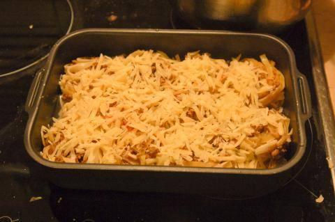 Затем протушенные гнезда перекладываем в другую тару (либо оставляем в той же сковороде), засыпаем все сверху сыром и отправляем в предварительно разогретую до 180 градусов духовку на 10-15 минут.