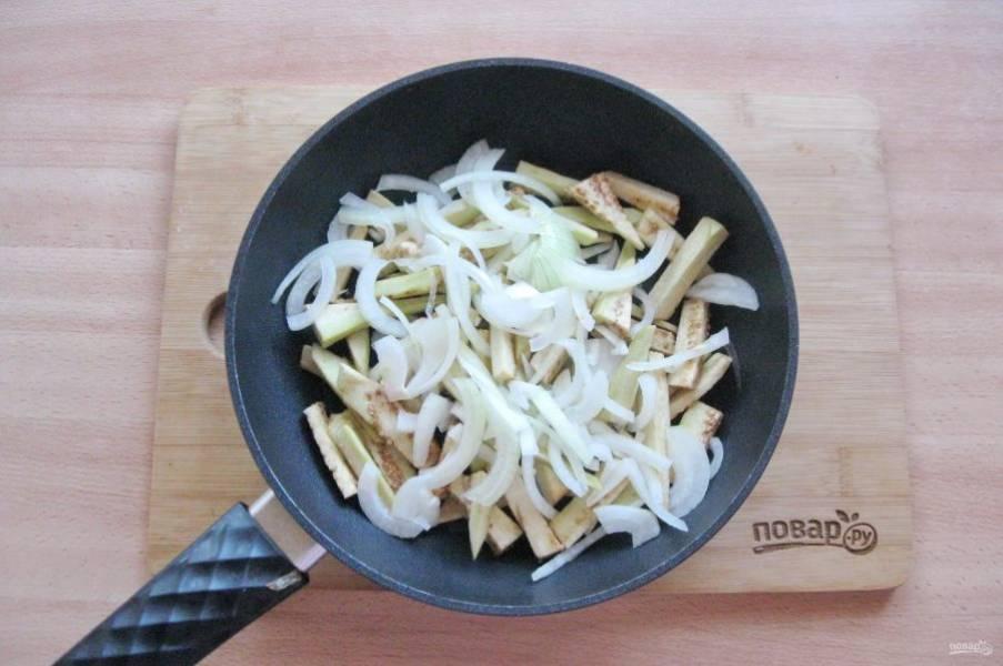 Репчатый лук очистите, помойте и нарежьте полукольцами. Добавьте в сковороду с баклажаном.