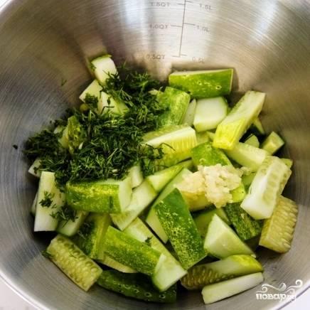 Добавляем к огурцам нарубленную зелень и измельченный чеснок.