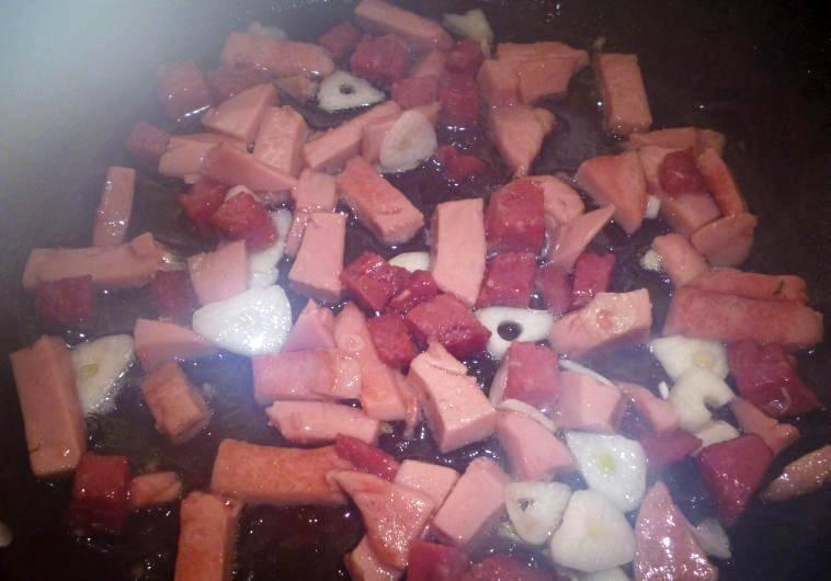 В сковороду наливаем растительное масло и обжариваем на нем колбасу и чеснок.