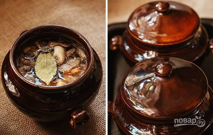 6. Для аромата сверху можно выложить лавровый листик. Влейте чистую воду, накройте крышечками и отправьте горшочки в разогретую до 190 градусов духовку.