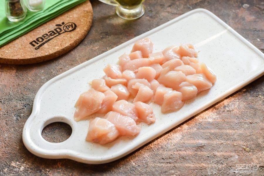 Ополосните куриное филе, нарежьте небольшими кусочками. В кастрюле доведите до кипения воду, опустите филе и доведите до кипения, снимите пенку. Варите филе 15 минут.