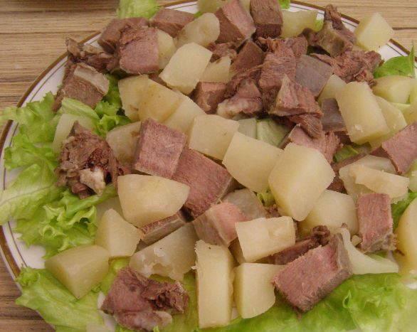 Сверху выложите кубики картофеля и отварного языка.