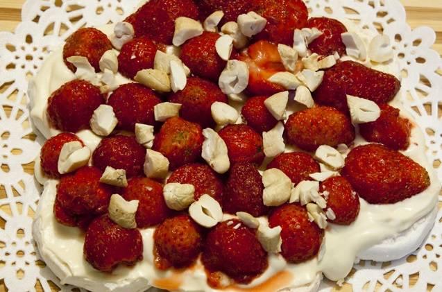 7. Орехи очистить от скорлупы и при желании измельчить до среднего размера. Выложить орехи на торт, равномерно распределяя их по поверхности.