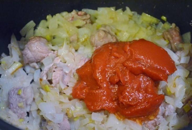 Смешайте муку с небольшим количеством воды и добавьте к мясу, а через минуту положите томатную пасту.