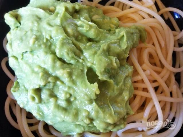 4. Далее переложите спагетти на сковороду, добавьте соус из авокадо. Помешивая, нагрейте пасту до тёплого состояния.