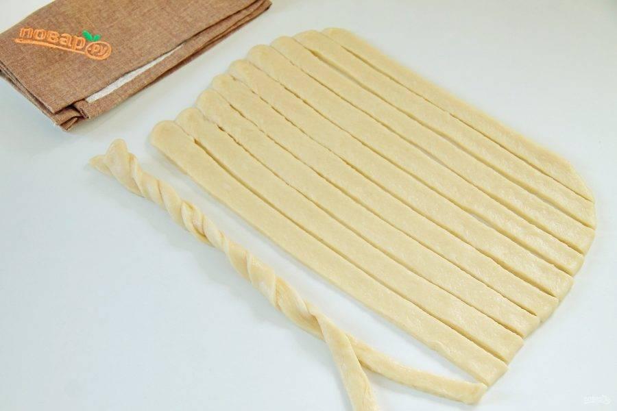 Вторую часть теста раскатайте на смазанной маслом поверхности, нарежьте полосками около 1 см шириной и переплетите по две полоски между собой.