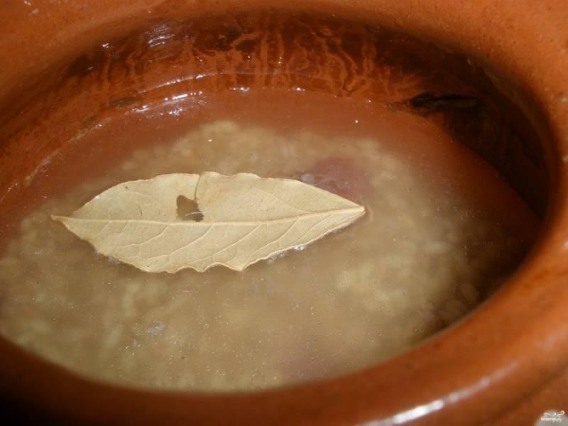 Перловку промойте хорошенько, выложите ее поверх мяса. Залейте водой так, чтобы покрывало перловку на 1,5 см. В каждый горшочек положите по лавровому листу.