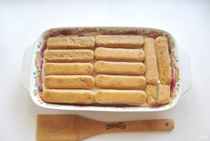 Обмакивая печенье в кофе с коньяком, выложите второй слой печенья.
