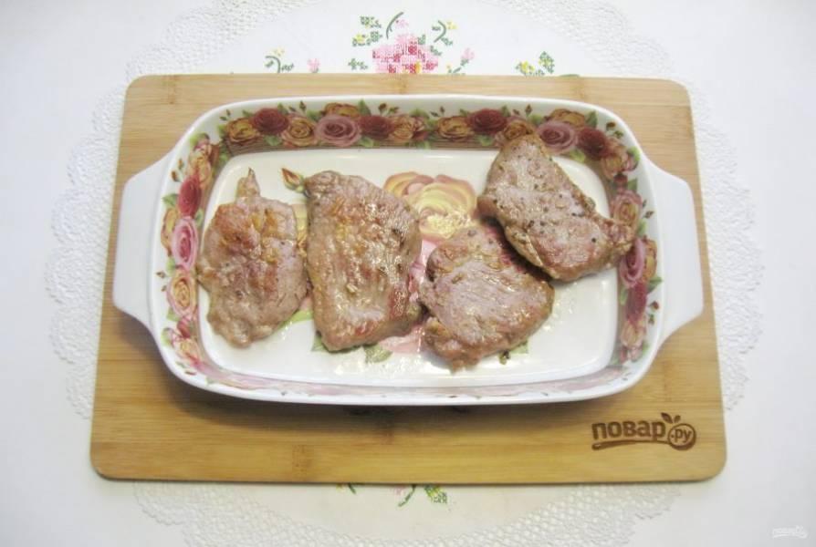 Жареную свинину выложите в форму для запекания, смазанную маслом.