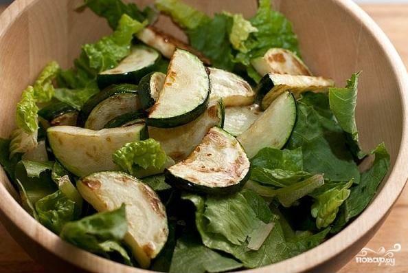 2. Промыть салат, обсушить и нарвать руками в салатник. Добавить жареные овощи.