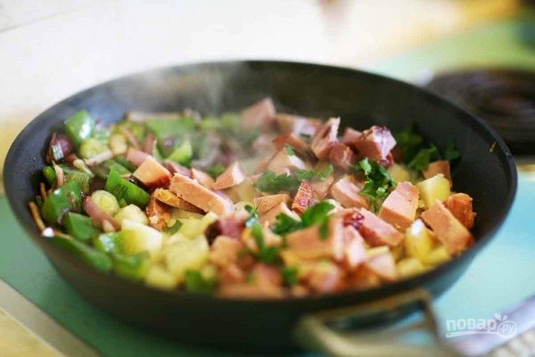 3.Нарежьте ветчину брусочками и добавьте в сковороду, измельчите петрушку и зеленый лук, выложите к остальным ингредиентам.