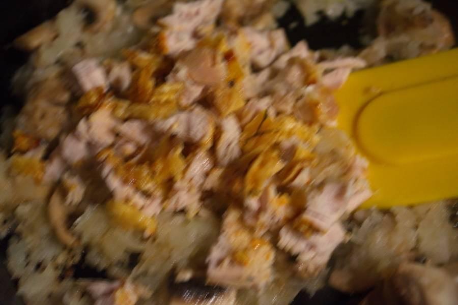 Добавьте готовое мясо курицы. Перемешайте. Обжарьте все вместе около 10 минут.
