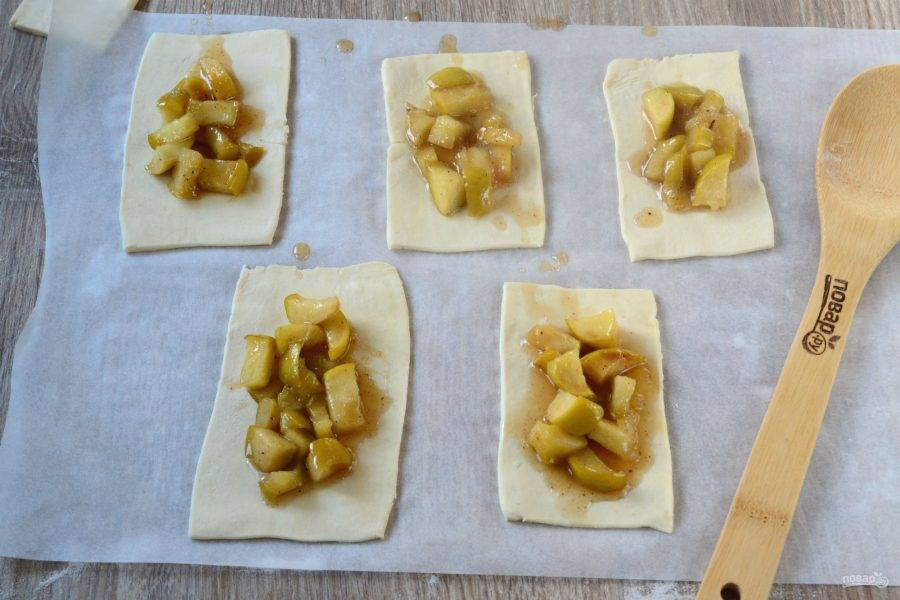На половину прямоугольников положите яблочную начинку, оставляя по краям примерно 5-7 мм.