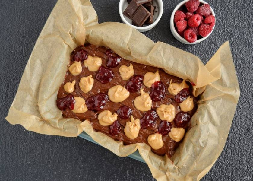Переложите тесто в форму для выпекания. Сверху чайной ложкой выложите арахисовую пасту и малиновое варенье в шахматном порядке.