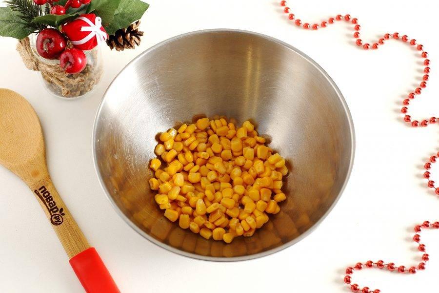 С кукурузы слейте жидкость и переложите ее в глубокую миску.