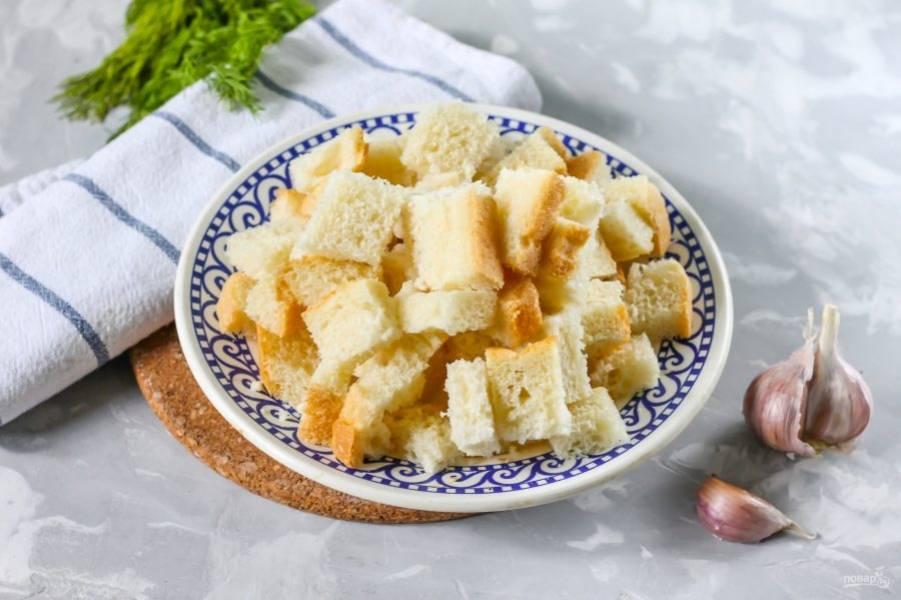 Ломтики белого, ржаного или черного хлеба нарежьте кубиками средних размеров. Крупная нарезка не прожарится, а мелкая - пригорит.