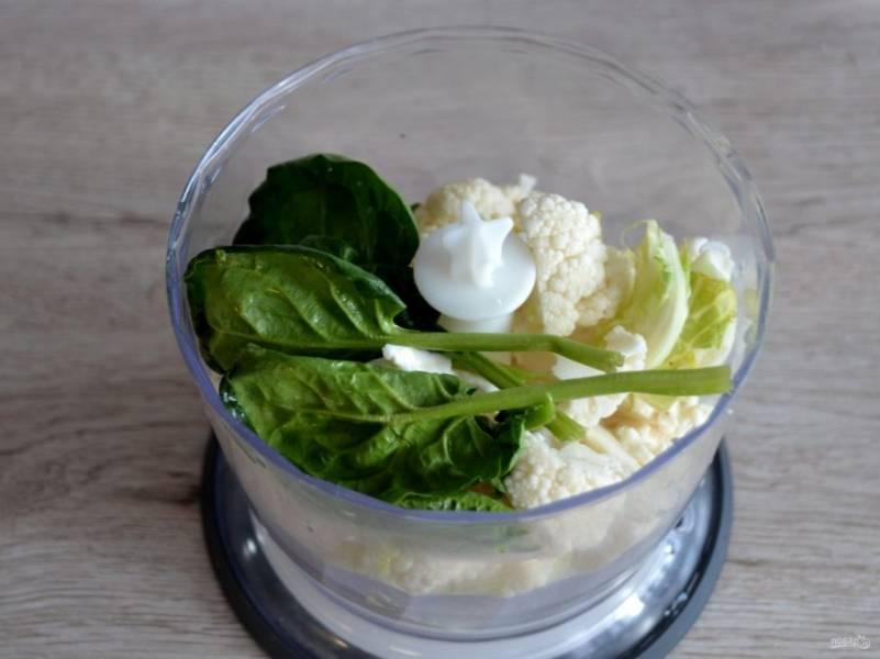 Сложите в чашу блендера цветную капусту и несколько листочков шпината.