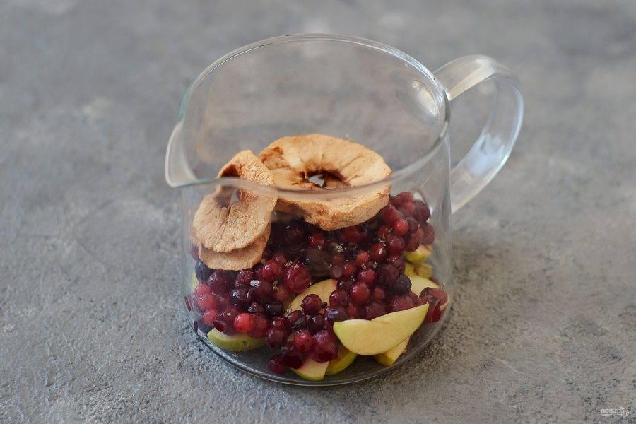 Выложите в чайник бруснику и клюкву, сушеные и свежие нарезанные яблоки, добавьте кардамон и сахар.