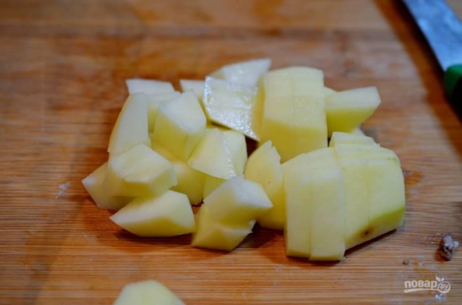 Картофель нарежьте кубиками и добавьте в кипящий бульон.