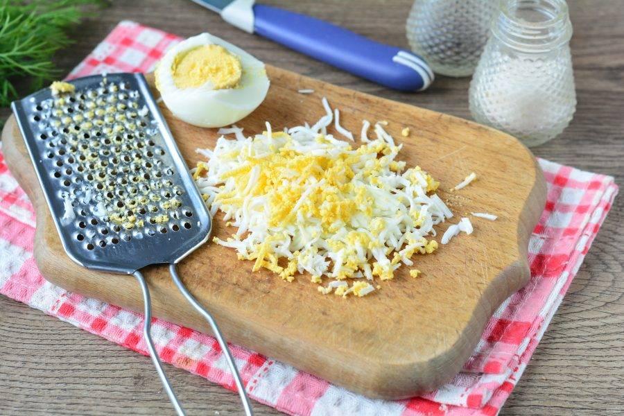 Куриное яйца сварите вкрутую, остудите и почистите. Натрите на мелкой терке.