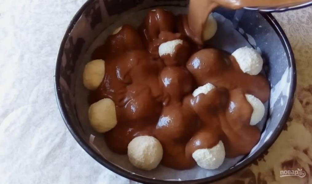 Залейте шарики шоколадным тестом. Выпекать пирог нужно в духовке при температуре 180 градусов 30-40 минут.