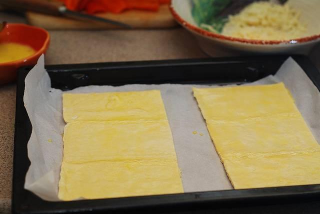 4. Слегка подтаявшее тесто нужно смазать взбитым яйцом, хорошо промазав края.