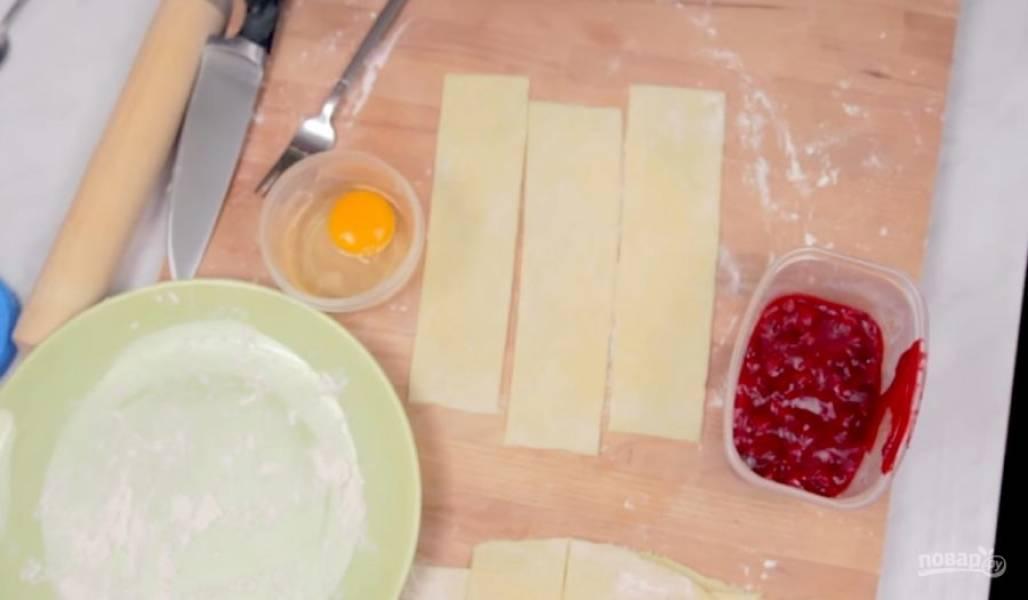 4. Тесто раскатайте в пласт толщиной примерно 3-5 мм, разрежьте его на длинные прямоугольники и на средину выложите начинку. Края теста смажьте яйцом, слегка взбитым с молоком, чтобы они лучше прилипли друг к другу.
