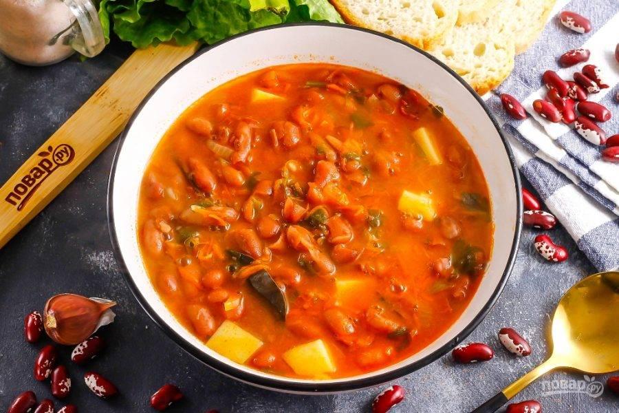 Разлейте фасолевый суп в пиалы или тарелки, подайте с хлебом, сухариками, пампушками.