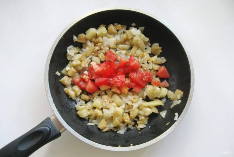 Помидор мелко нарежьте и отправьте в сковороду.