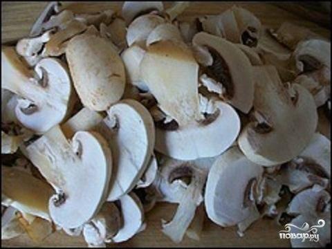 1.Подготовим необходимые нам продукты. Шампиньоны нужно вымыть хорошо в холодной воде и немного обсушить. После этого нарежем грибы тонкими пластинками.