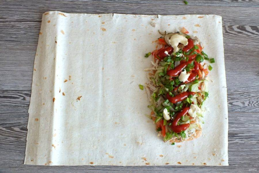 На курицу нарезанные овощи. В нескольких местах выложите кетчуп и майонез. Посыпьте нарезанным зеленым луком.
