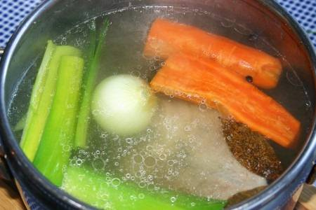 4. По-настоящему вкусным и ароматным бульон делают овощи. Морковь необходимо вымыть и очистить, порезать пополам. Луковицу можно очистить или просто вымыть и оставить в шелухе (таким образом лук отдаст не только вкус бульону, но и цвет). Лук-порей также вымыть. Прекрасно подходит для бульона также сельдерей. Примерно через час в бульон можно добавить овощи. Также отправить туда вымытый лавровый лист и душистый перец.