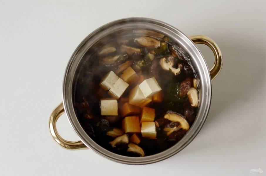 Переложите в кастрюлю тофу и прогрейте суп еще 3 минуты.