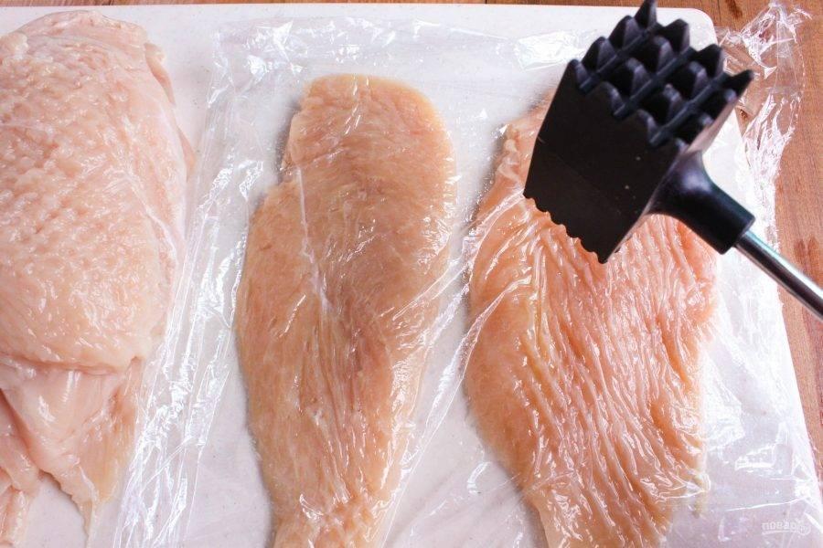 1.Вымойте куриное филе и разрежьте вдоль на 2 части. Выложите все на разделочную доску, накройте пленкой и слегка отбейте молоточком.