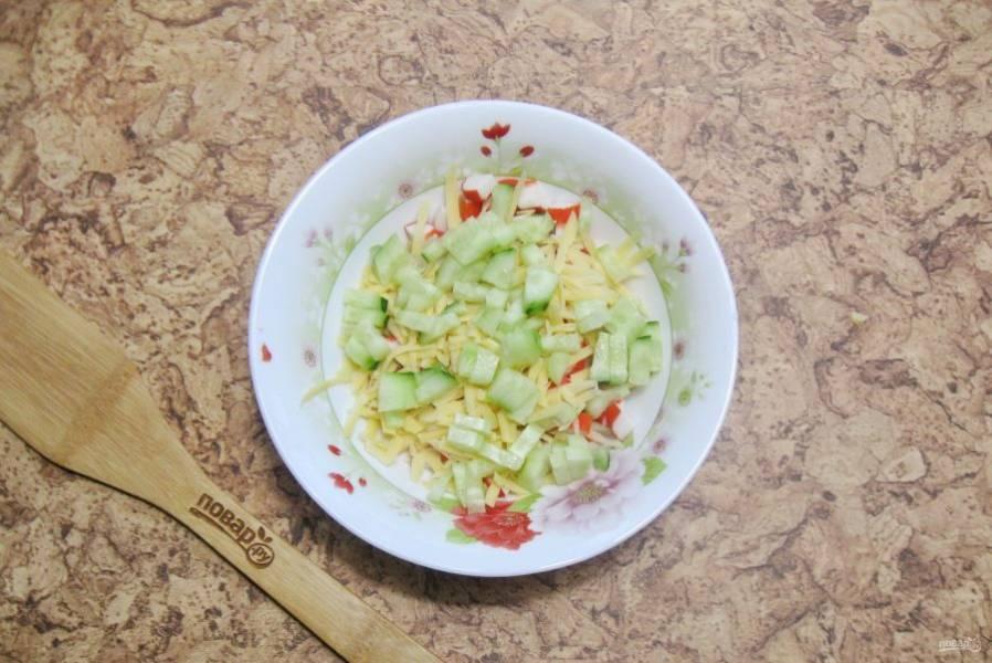 Огурец помойте, очистите и нарежьте кубиками. Выложите в салатник.