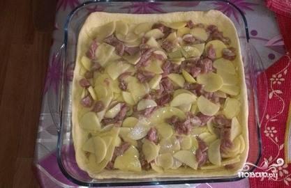 Если вы используете магазинное готовое тесто, то его необходимо предварительно разморозить. Разделите его после этого на две части таким образом, чтобы одна была больше другой. Большую часть раскатайте и выложите на противень. Сверху на тесто положите начинку из картошки и мяса.