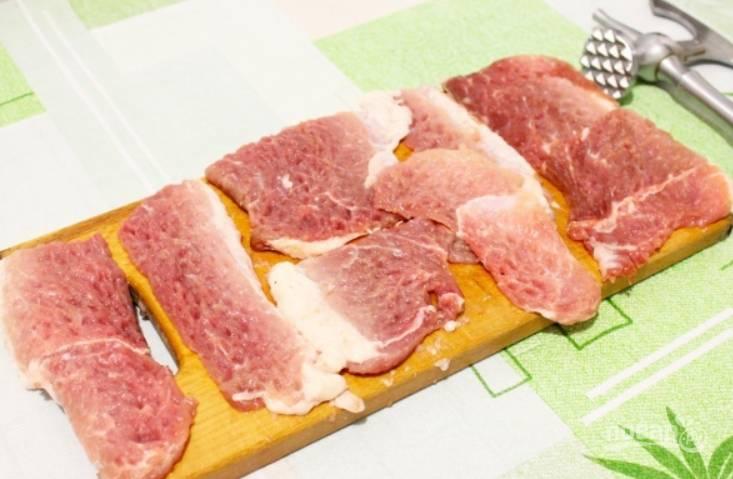 Свинину промойте и обсушите. Нарежьте мясо порционными кусочками, слегка отбейте. Посолите и поперчите по вкусу.