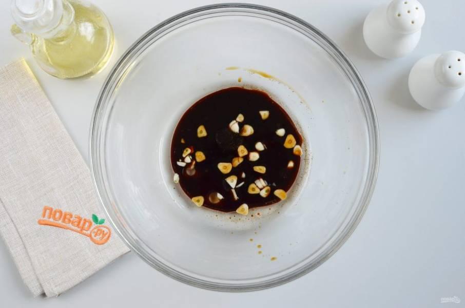 Готовим маринад. Для этого в большую миску налейте 2 ст.л. растительного масла, 100 мл. классического соевого соуса, 6 зубчиков чеснока (крупно порезанных). Перемешайте хорошо.