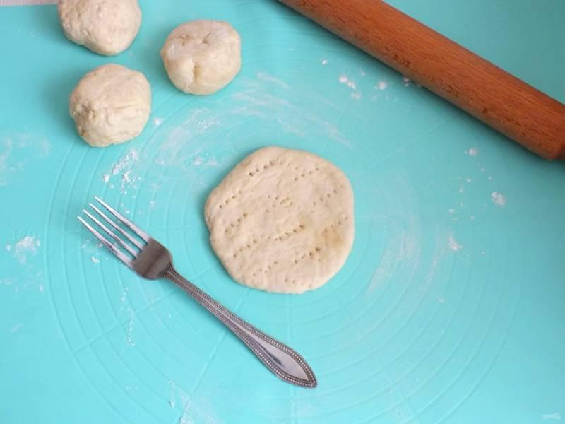 Возьмите одну часть и раскатаете в лепешку толщиной 0,5 см. Проколите вилкой по всей поверхности заготовки.