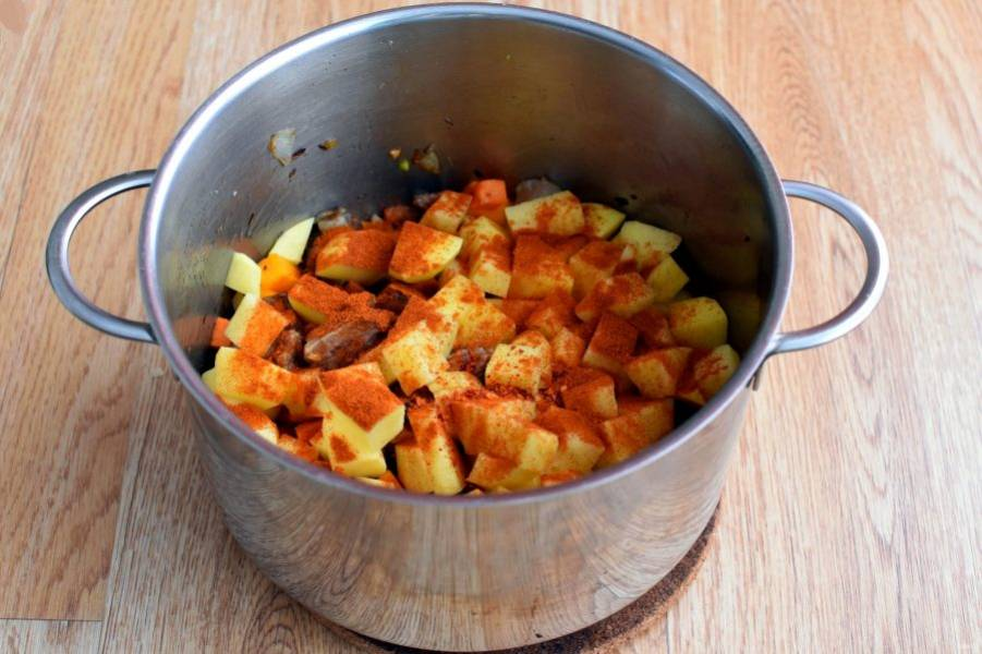 Добавьте картофель и тыкву, нарезанные кубиками вдвое крупнее моркови. Посыпьте паприкой и обжаривайте до окрашивания жира в красный цвет.