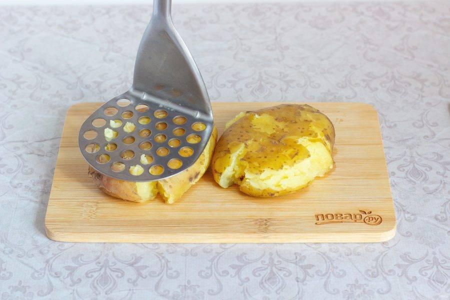 Горячий вареный картофель придавите толкушкой.