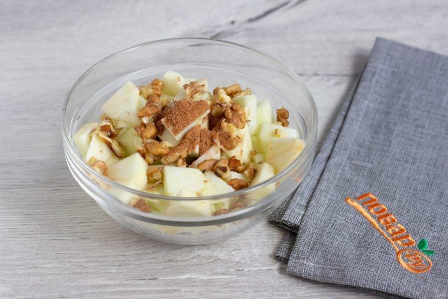 Яблоки помойте, очистите от сердцевины и кожуры, нарежьте небольшими кусочками. Орехи измельчите и добавьте вместе с корицей к яблокам.