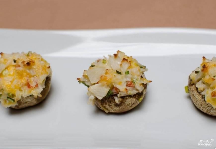 Закуску выпекаем при 180 градусах около 20 минут. Готовые шампиньоны фаршированные крабовыми палочками выкладываем на блюдо и подаем к столу в горячем или холодном виде. Приятного аппетита!